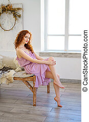 beautiful red-haired woman sitting in the Studio in a sad mood