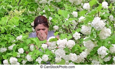 Beautiful red-haired woman sneezes and rubs her nose while standing next to a blossoming apple tree in a park. Seasonal allergic rhinitis. The girl suffers from an allergy to pollen