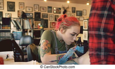 Beautiful red haired woman tattoo artist tattooing picture on leg of young girl client in studio