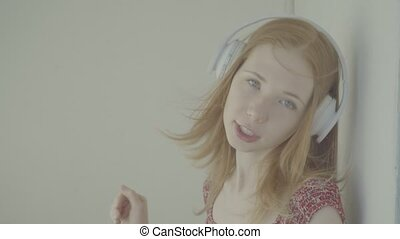 Beautiful red-haired woman with headphones listen to music