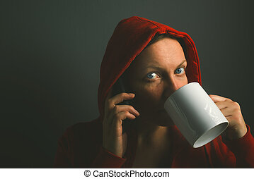 Beautiful red hooded woman drinking coffee and using mobile phon