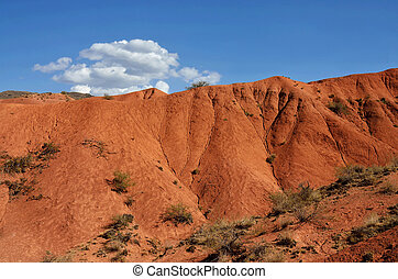 Beautiful red Konorchek ravine with small white cloud against blue sky, Issyk-Kul region, Central Asia, famous hiking place