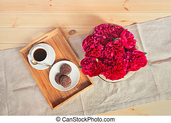 Beautiful red peony flowers, cup of coffee and chocolate cookies on wooden table. Top view.