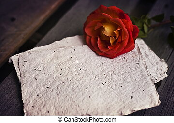 Beautiful red rose on wooden rustic background with handmade...