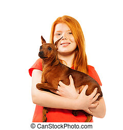 Beautiful red smiling girl with dog on her hands