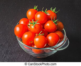 beautiful red tomatoes cherry in transparent salad bowl on black slate background, close up