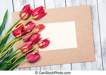 Beautiful red tulips , empty paper sheet on wooden background. Mother's day.