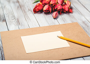 Beautiful red tulips , empty paper sheet on wooden background. Mother's day. Selective focus.