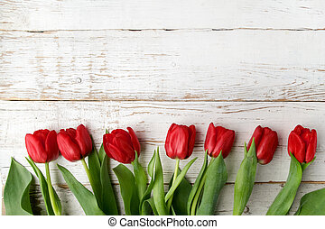 beautiful red tulips on white wooden background. Top view.