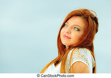 Beautiful redhaired girl on beach, portrait