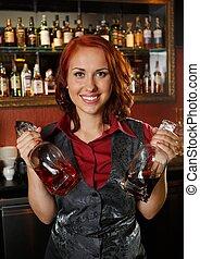 Beautiful redhead barmaid with bottles behind bar counter