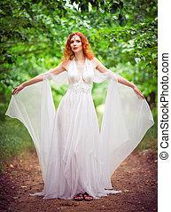 Beautiful redhead elf woman wearing white dress in a garden