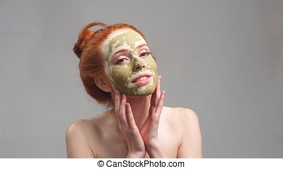 Beautiful redhead girl applying facial clay mask. Beauty...