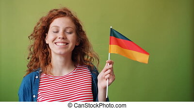 Beautiful redhead girl holding German flag smiling on green...