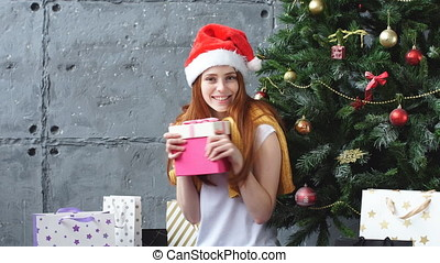 Beautiful redhead girl in Santa hat hugs gift box. -...