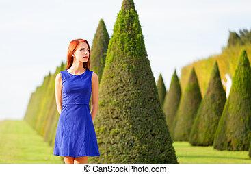Beautiful redhead girl in Versailles park
