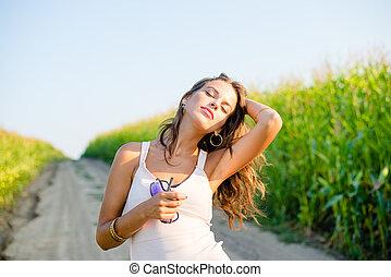 Beautiful redhead girl in white dress walking by corn field