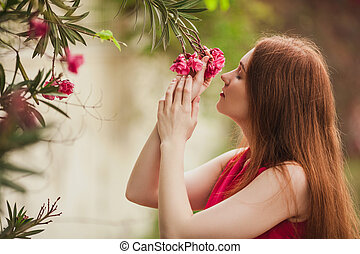 Beautiful redhead girl inhales the aroma of the flower. Red flower growing on a tree.