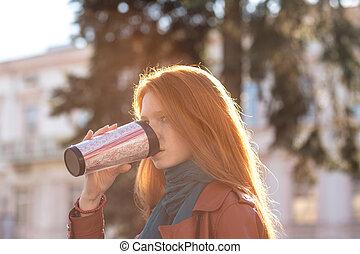 Beautiful redhead lady drinking coffee from tumbler