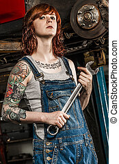 Beautiful redhead mechanic fixing brakes