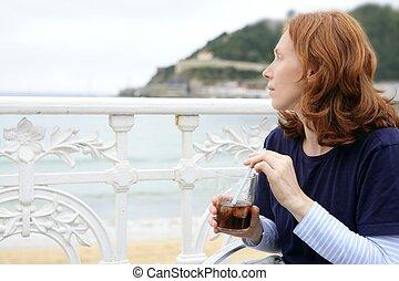 Beautiful redhead woman drinking beverage