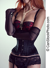 Beautiful redhead woman in corset, pinup red bra and sheer glove