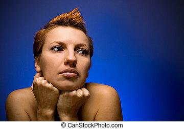 Beautiful redhead woman on blue background