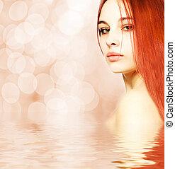 Beautiful redhead woman reflected in water