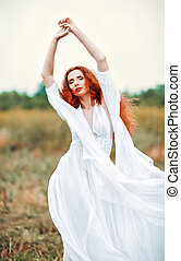 Beautiful redhead woman wearing white dress in a field - ...