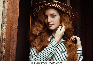 Beautiful redhead woman with long curly hair in straw hat posing near the old door