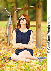 Beautiful redhead women with bike in Versailles gardens. France