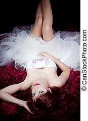 Beautiful redheaded woman lying on a bed of roses in black...