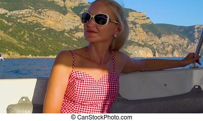 Beautiful relaxing on a boat, an adult with tender lips around the sea, the concept of webinar activities in sunglasses beautiful horizon