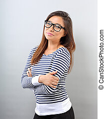 Beautiful relaxing positive woman in glasses looking with thinking look on blue background with empty copy space