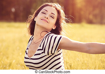Beautiful relaxing woman enjoying fresh air in sunny summer day on nature background with closed eyes