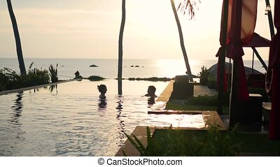 Beautiful restaurant on the beach. A romantic place for lovers. A man and a girl are swimming in the pool. Sunset