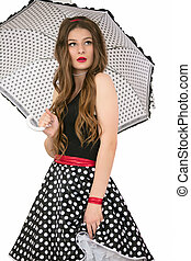 Beautiful retro girl. Woman in a skirt with polka dots with an umbrella.