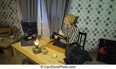 Beautiful retro seamstress girl sews cloth with old manual hand sewing machine. Woman working at home or workshop at night with kerosene lamp, listens music on vinyl plate, gramophone or phonograph