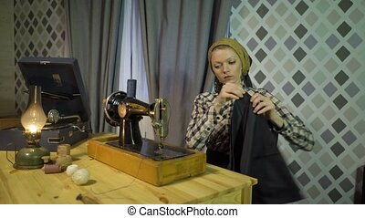 Beautiful retro seamstress girl sews cloth with old manual hand sewing machine. Woman working at home or workshop at night with kerosene lamp, listens music vinyl plate, gramophone or phonograph