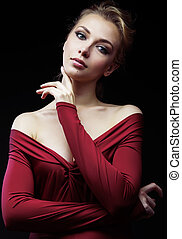 beautiful rich blond woman in elegant dress on black background