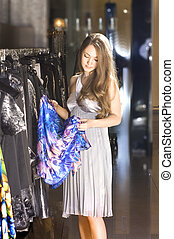 rich woman chooses a dress in a boutique