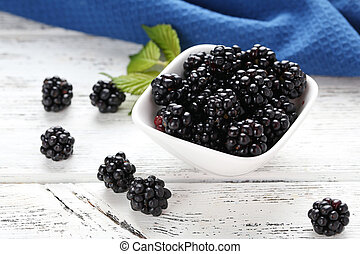 Beautiful ripe blackberry in bowl on white wooden background