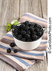 Beautiful ripe blackberry in cup on grey wooden background