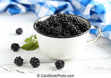 Beautiful ripe blackberry in cup on white wooden background