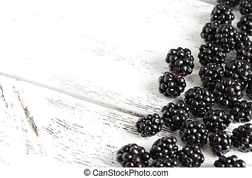 Beautiful ripe blackberry on white wooden background