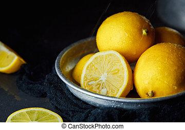 Beautiful ripe lemons in plate on a black background