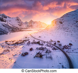 Beautiful road in snowy mountains in winter at sunset