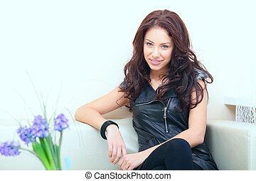 Beautiful rock-n-roll woman sitting on a sofa