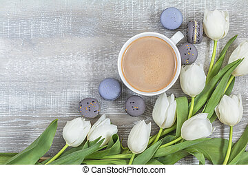 Cup of coffee, white tulips and gray macaroons on light wooden surface