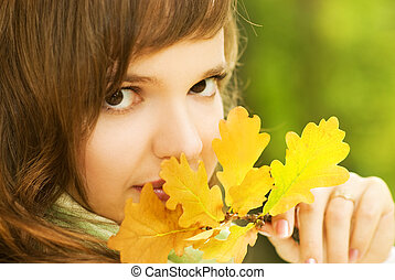 Beautiful romantic brunette with golden autumn leaf close-up portrait